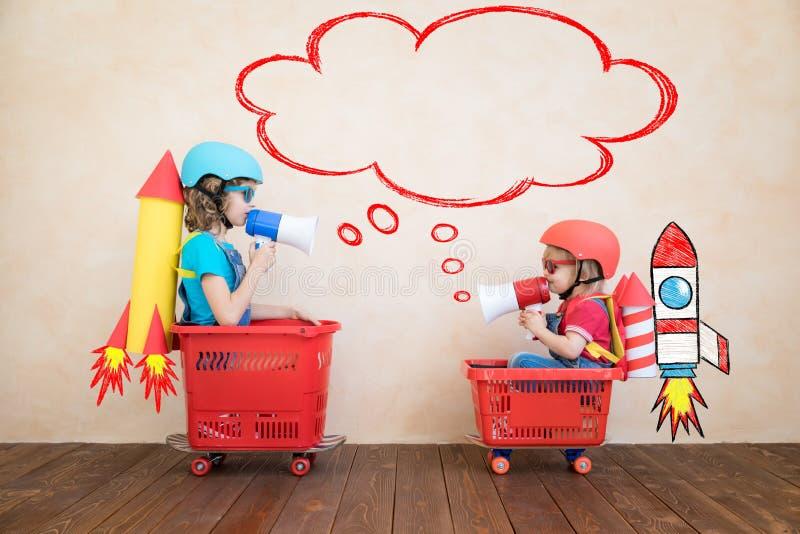 Enfants heureux conduisant la voiture de jouet ? la maison image stock