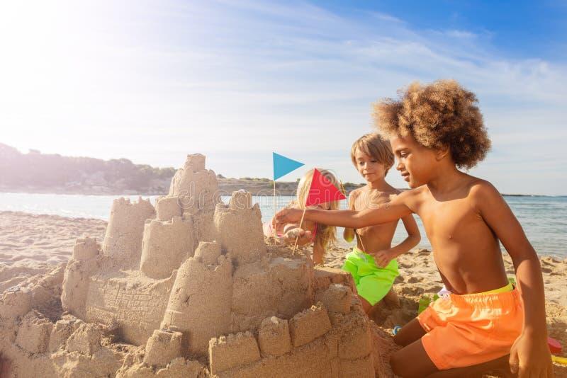 Enfants heureux décorant des tours de pâté de sable avec des drapeaux photo stock