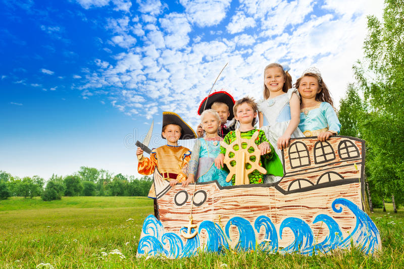 Enfants heureux dans des costumes se tenant sur le bateau photographie stock