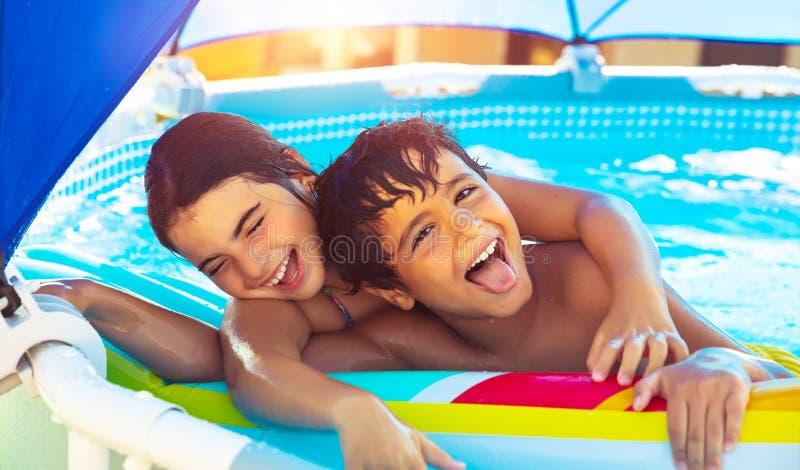 Enfants heureux dans la piscine image stock
