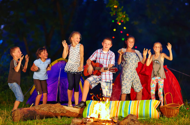 Enfants heureux dansant autour du feu de camp photographie stock libre de droits