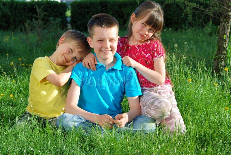 enfants heureux enfoncés dans l'herbe image stock