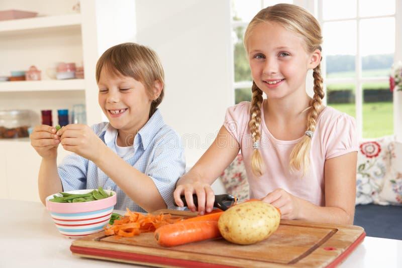 Enfants heureux enlevant des légumes dans la cuisine images libres de droits
