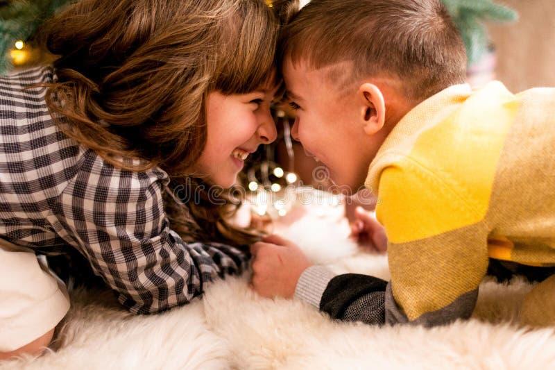 Enfants heureux et riants - frère et soeur près de l'arbre de Noël photos stock