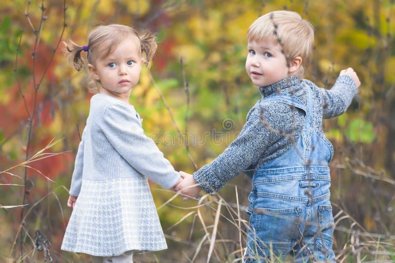 Enfants heureux extérieurs à l'automne, tenant des mains A la date photographie stock