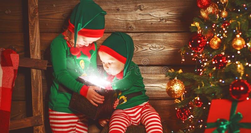 Enfants heureux frère et elfe de soeur, aide de Santa avec Chri photos stock