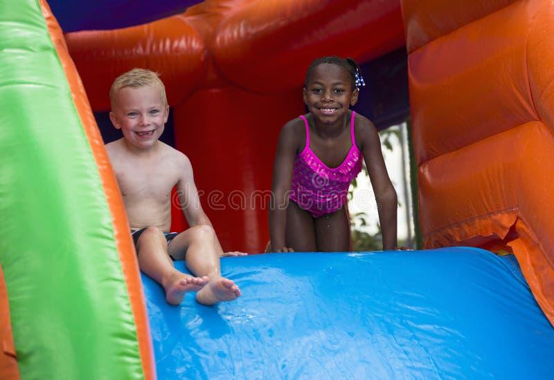 Enfants heureux glissant en bas d'une maison gonflable de rebond photos libres de droits