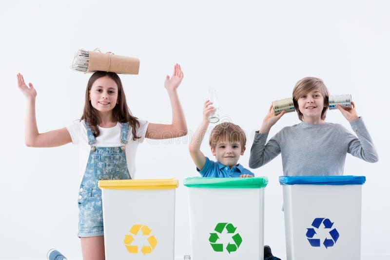 Enfants heureux isolant des déchets de ménage photographie stock libre de droits