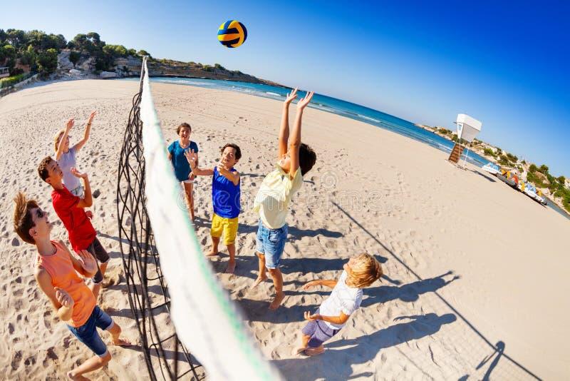 Enfants heureux jouant au volleyball sur la plage photographie stock libre de droits