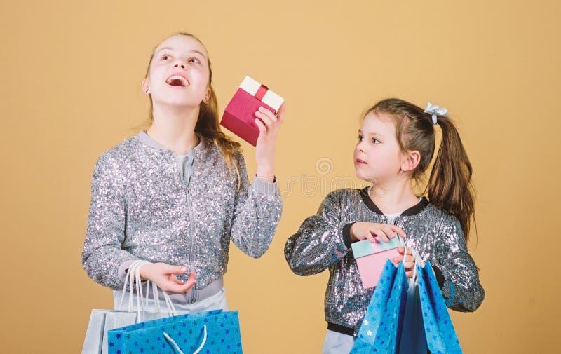 Enfants heureux Peu soeurs de fille avec le bo?te-cadeau fraternit? Achats de vacances mode d'enfant employ? de magasin avec photo libre de droits