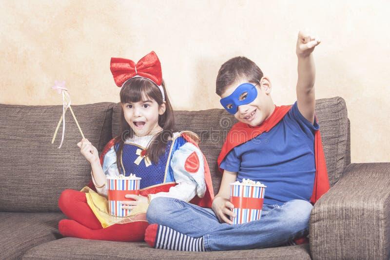 Enfants heureux regardant la TV à la maison images stock