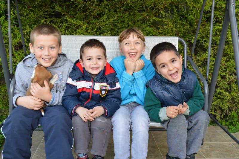 Enfants heureux s'asseyant ainsi qu'un chiot photo libre de droits