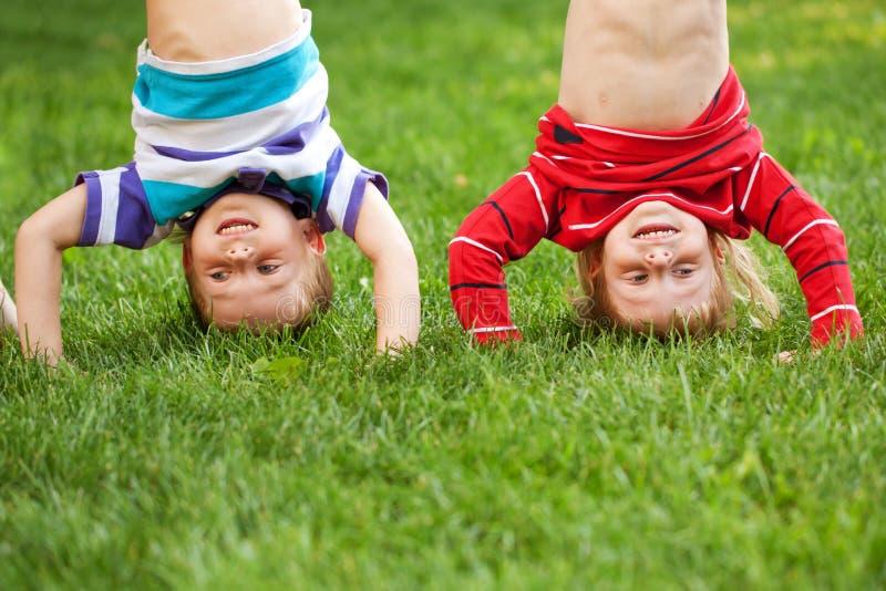 Enfants heureux se tenant à l'envers sur l'herbe. photos stock