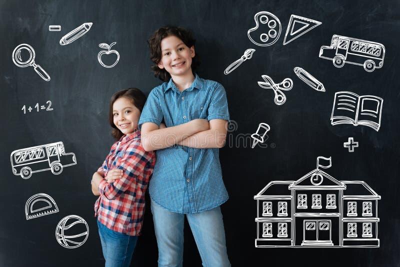 Enfants heureux se tenant avec leurs bras croisés et école de attente photo stock