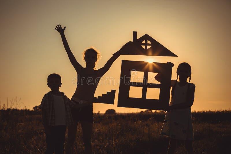 Enfants heureux se tenant sur le champ au temps de coucher du soleil image libre de droits