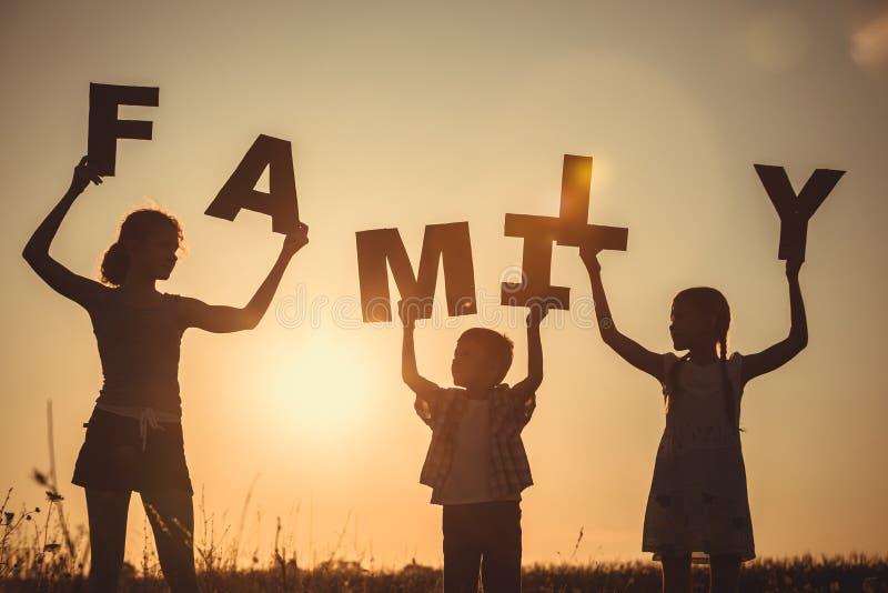 Enfants heureux se tenant sur le champ au temps de coucher du soleil photos libres de droits