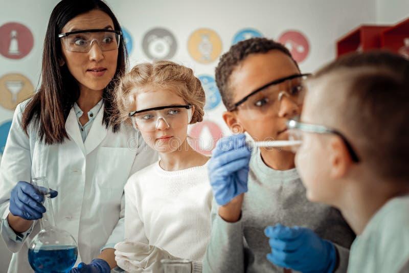 Enfants internationaux jouant ainsi que le réactif chimique images stock