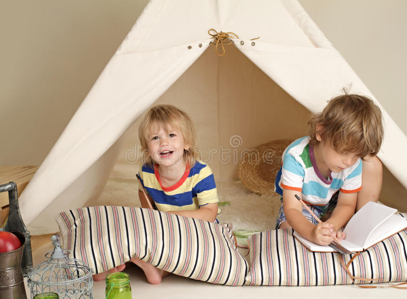 Enfants jouant à la maison à l'intérieur avec une tente de tipi images libres de droits