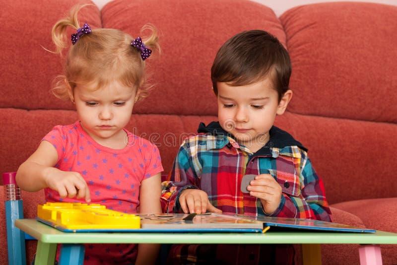 Enfants jouant à la table photo stock
