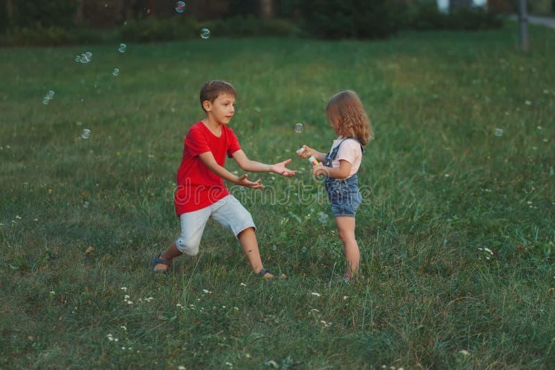 Enfants jouant avec des bulles de savon en parc images stock
