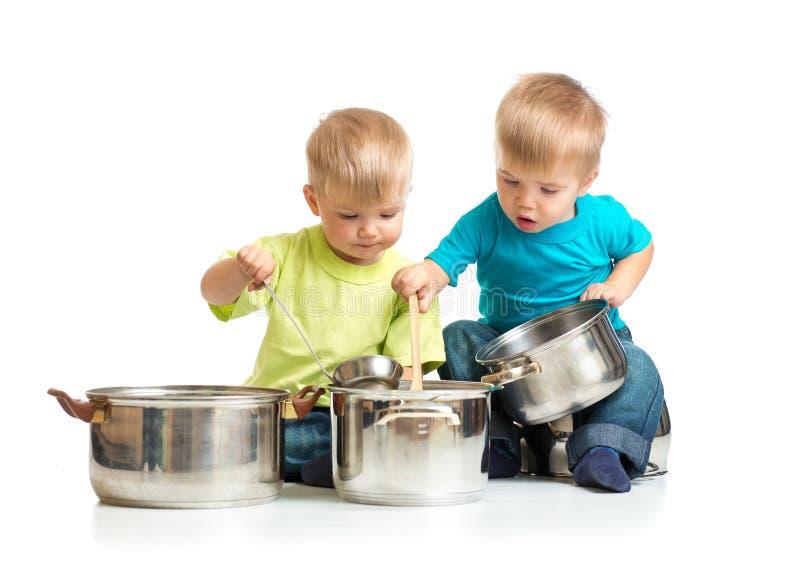 Enfants jouant avec des casseroles comme ils font cuire ensemble photographie stock libre de droits