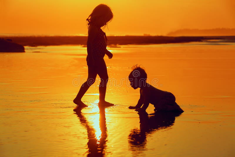 Enfants jouant avec l'amusement sur la plage de mer de coucher du soleil images libres de droits