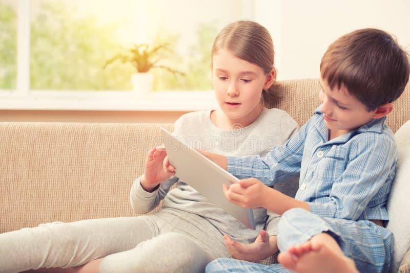 Enfants jouant avec le comprimé numérique image libre de droits