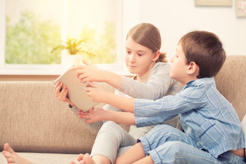 Enfants jouant avec le comprimé numérique photo stock