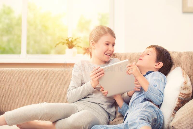 Enfants jouant avec le comprimé numérique images stock