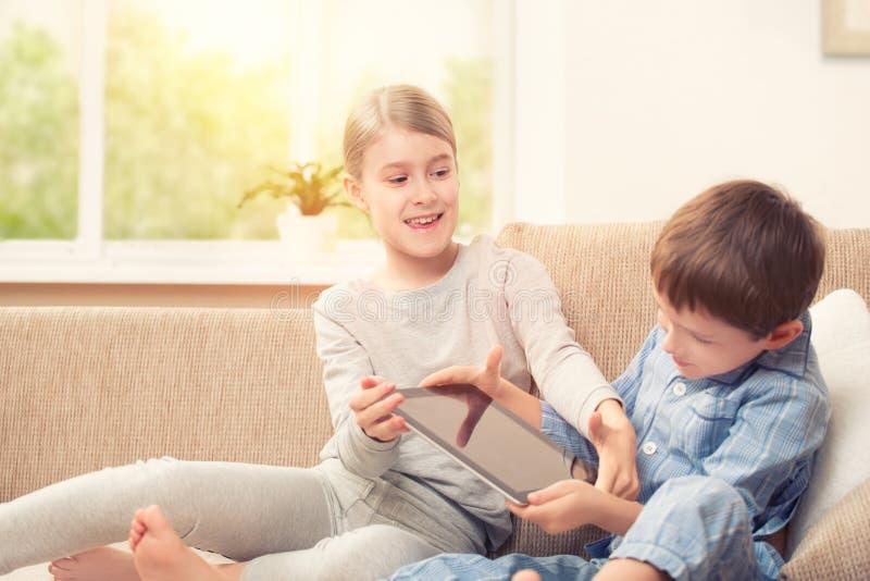 Enfants jouant avec le comprimé numérique photographie stock libre de droits