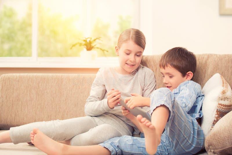 Enfants jouant avec le comprimé numérique images libres de droits