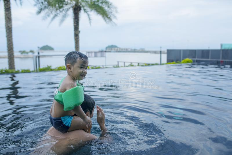 Enfants jouant avec le père dans la piscine d'eau photographie stock