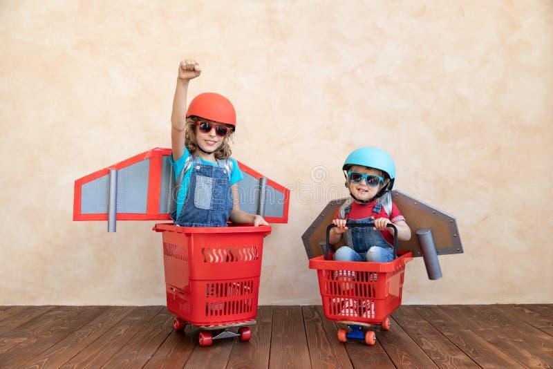 Enfants jouant avec le paquet de jet à la maison image libre de droits
