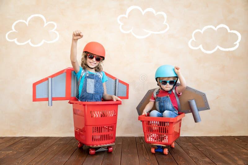 Enfants jouant avec le paquet de jet ? la maison photo libre de droits