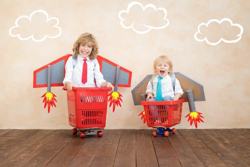 Enfants jouant avec le paquet de jet ? la maison image stock