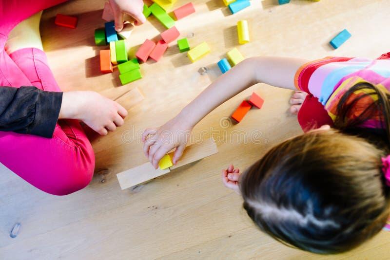 Enfants jouant avec les blocs en bois colorés photos libres de droits