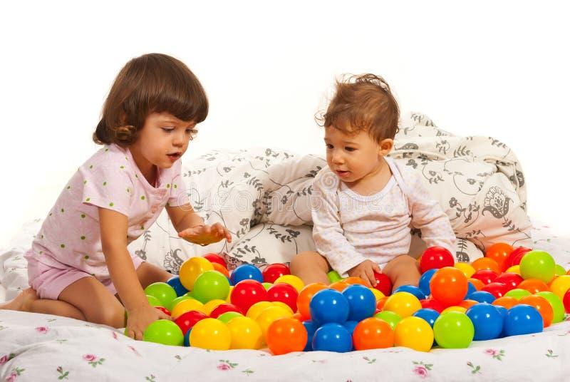 Enfants jouant avec les boules colorées photos stock