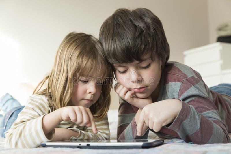 Enfants jouant avec un comprimé numérique images stock