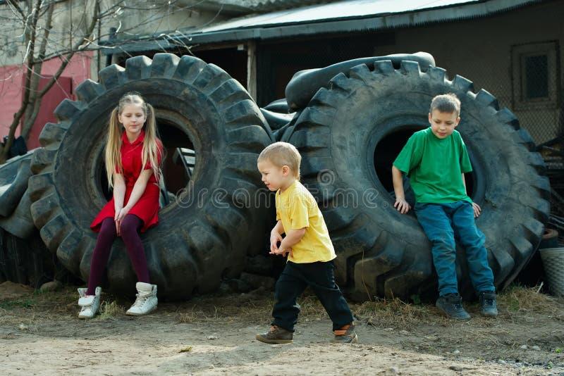Enfants jouant dans des pneus d'entrepôt de ferraille image libre de droits