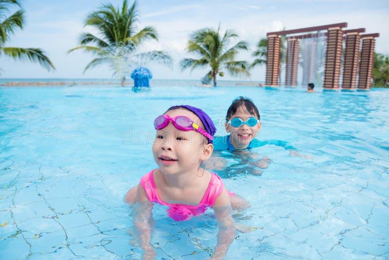 Enfants jouant dans la piscine dans le jour ensoleillé photos libres de droits