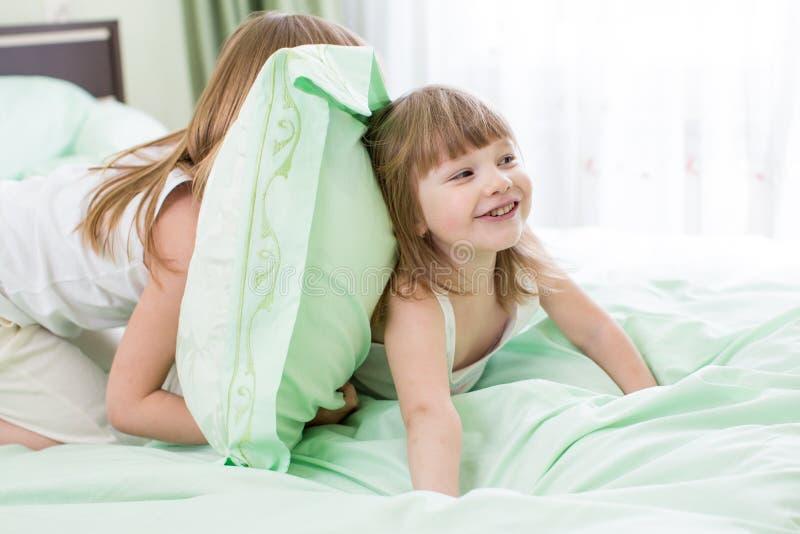 Enfants jouant dans le lit photos stock