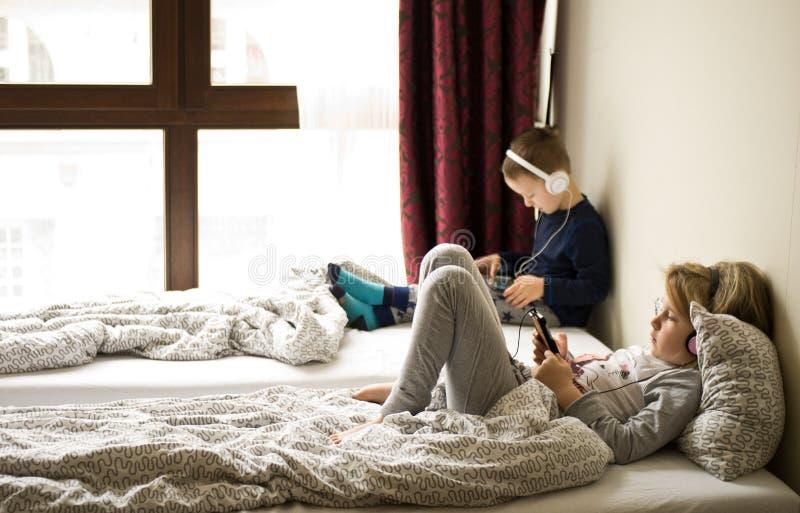 Enfants jouant dans le lit avec leurs comprimés et téléphones photos libres de droits