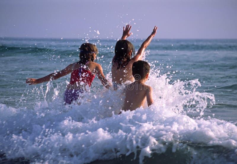 Enfants jouant dans les ondes photographie stock