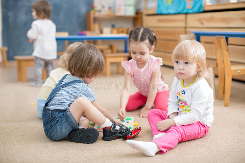 Enfants jouant des jeux dans la salle de jeux de jardin d'enfants image libre de droits