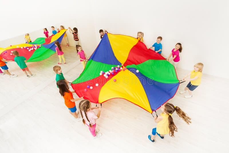 Enfants jouant des jeux de parachute dans le gymnase léger images libres de droits