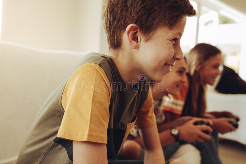 Enfants jouant des jeux vidéo à la maison images libres de droits
