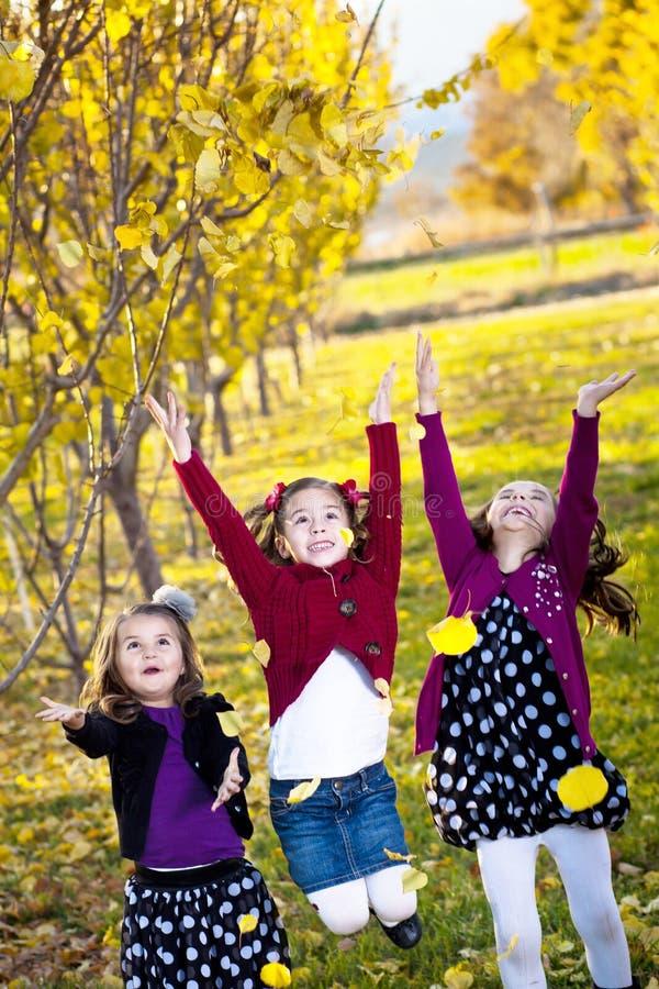 Enfants jouant en automne des lames photos stock
