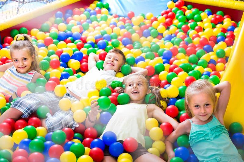 Enfants jouant ensemble dans la piscine avec la boule multicolore en plastique images libres de droits