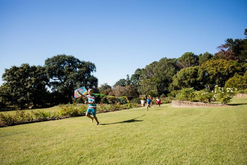 Enfants jouant ensemble pendant un jour ensoleillé avec un cerf-volant photos stock