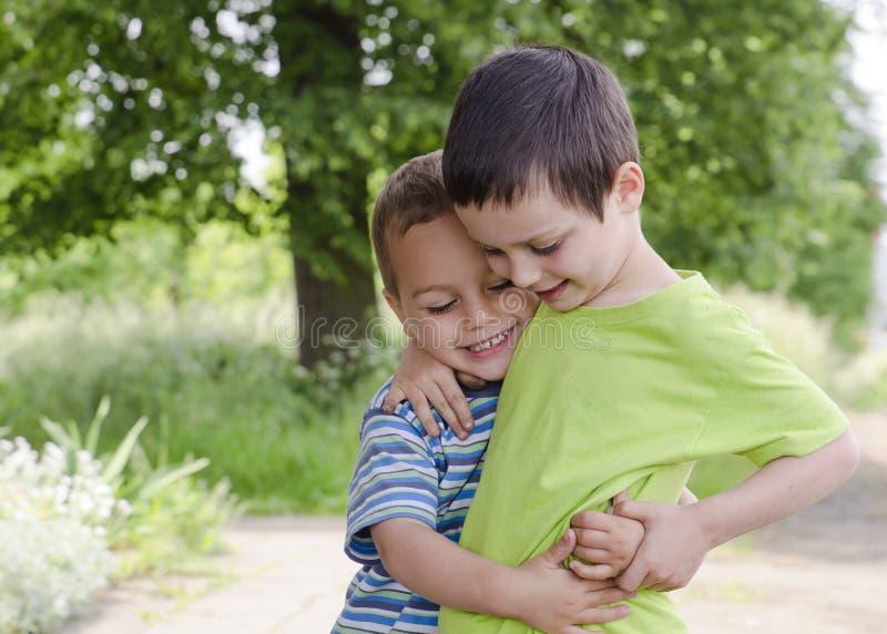Enfants jouant et étreignant image stock